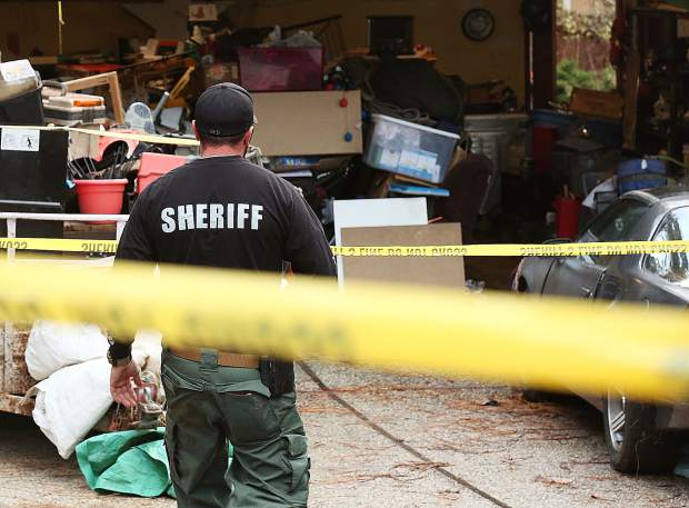 A Nevada County Sheriff's officer enters the crime scene Wednesday evening near Lawrence Way and Oscar Drive in Alta Sierra.