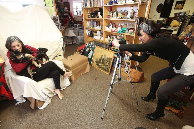 Sandra Boyd takes Christmas-themed portraits of dogs and their owners Saturday at Rescue For Pet Sake in Grass Valley.