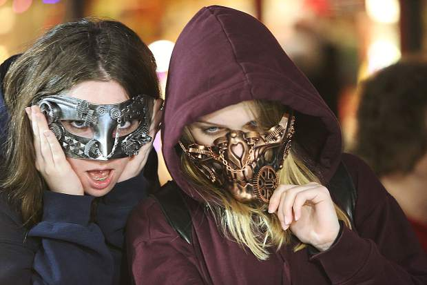 Sacramento's Eden Reader and Natalie Appel try on masks made by Pamela Devine of Devine Gifts, a craft booth vendor for the past 17 years at Victorian Christmas.