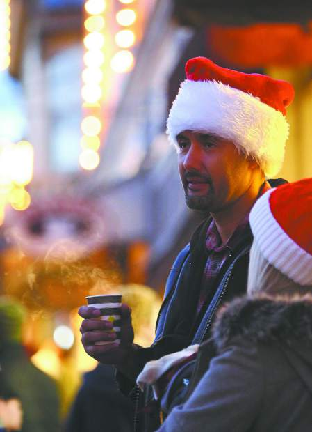 Yuba City's Dewayne Debbs sips on a cup of hot mulled wine along Broad Street Sunday evening during Nevada City's first Victorian Christmas of the 2018 holiday season. Wednesday night from 6 to 9 p.m. is the next scheduled Victorian Christmas street faire.