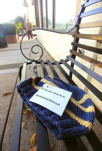"""The fourth annual """"warmth bombing"""" of downtown Grass Valley by Nevada County Random Acts of Warmth happened Friday morning. Nevada County Random Acts of Warmth is a small, casually organized, anonymous group of Nevada County peeps who leave (mostly hand-knitted) scarves and hats in random public places as gifts to the community. They planned to distribute more than 50 items this year, primarily on Mill Street and on Main Street between South Church and South Auburn. These are given in the spirit of the many holidays celebrated at this time of year and are intended to be taken by anyone who can use them. One such knitted hat sits on a bench in front of the Bret Harte Retirement Home Friday morning with the words,"""