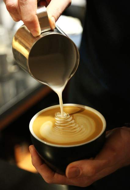 A latte is poured by City Council owner Josh Henry Wednesday afternoon at his coffee shop on the corner of Broad and Pine streets in downtown Nevada City.