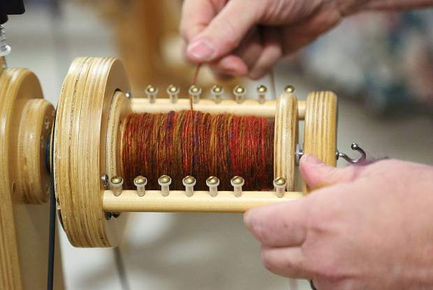 A spool of yarn is made from scratch with a traditional spinning wheel and strands of sheep's wool.