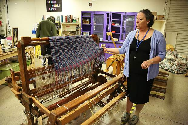 Leslie Whitcomb shows off a donated weavers loom from the 30s and 40s that was donated to the Fiber Arts program and is very useful.