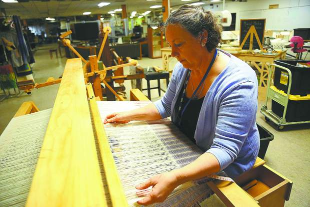 Grass Valley's Leslie Whitcomb throws the shuttle on a donated loom earlier this month at The Curious Forge off of Bitney Springs Road.