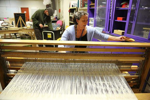 Leslie Whitcomb works on a project on a loom donated to the Curious Forge's Fiber Arts program.