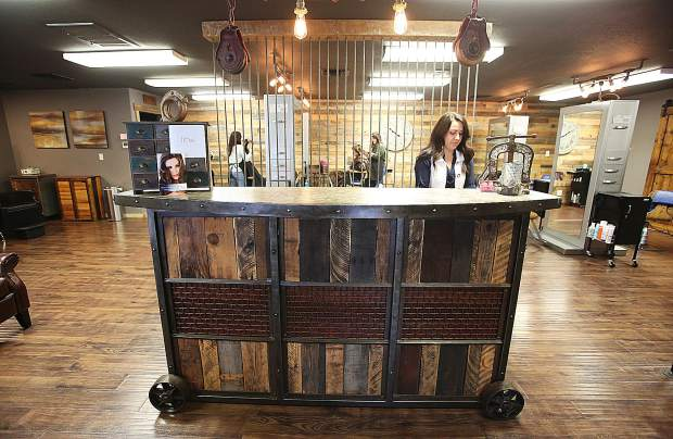 Hairstylists set their appointments at the front counter, constructed out of reclaimed rustic material.
