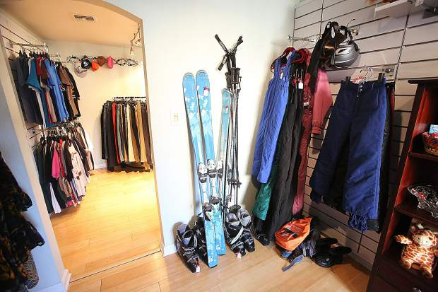 A room with specially marked items include skis, poles, winter gear and other items.