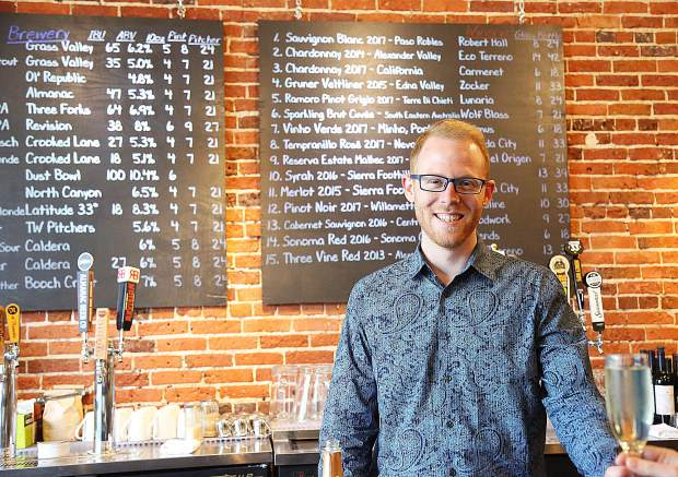 The Pour House bar manager Thomas Hall stands in front of a menu of different drinks available at the new downtown Grass Valley establishment.