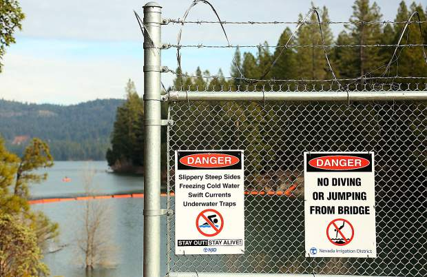 Signs discourages folks from jumping into the Scotts Flat Reservoir from the spillway path, however some around the end of the fence in order to access the jump point.