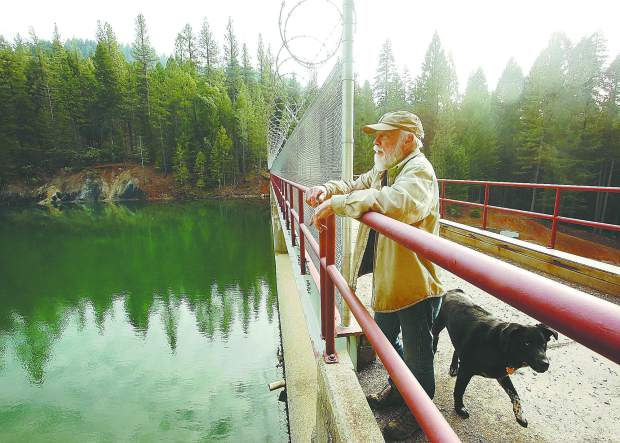 Cascade Shore's Mike Fitzwater pauses during a walk with his dog Osha, to show where youth climb over a railing in order to bypass a chain link fence and razor wire in efforts to jump off of the bridge. NID erected a fence on the Cascade Shores side of the dam, but not on the side accessible from the campgrounds.