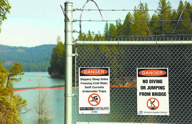 Clear signage discourages folks from jumping into the Scotts Flat Reservoir from the spillway path, however now daring youth climb around the end of the fence in order to access the jump point.