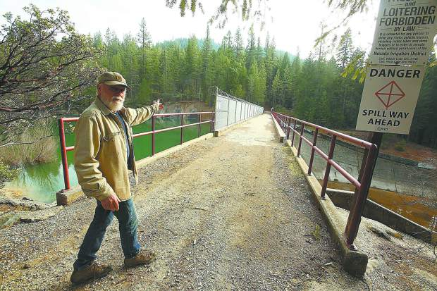 Cascade Shore's Mike Fitzwater, a regular user of the bicycle and pedestrian path, shows where youth jump a hand rail to get into Scotts Flat Reservoir from the dam's spillway.