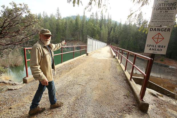 Cascade Shores' Mike Fitzwater, a regular user of the bicycle and pedestrian path, shows where some people jump a hand rail to get into Scotts Flat Reservoir from the dam's spillway.