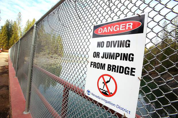 Clear signage discourages folks from jumping into the Scotts Flat Reservoir from the spillway path, however sometimes people climb around the end of the fence in order to access the jump point.