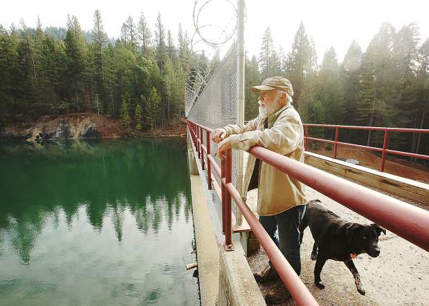 Cascade Shores' Mike Fitzwater pauses during a walk with his dog Osha, to show where some people climb over a railing in order to bypass a chain link fence and razor wire in efforts to jump off of the bridge. NID erected a fence on the Cascade Shores side of the dam, but not on the side accessible from the campgrounds.