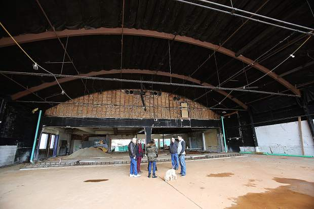 Center For The Arts remodel project personnel discuss the center's progress last week, showing the frame of the former car dealership that once occupied the space.