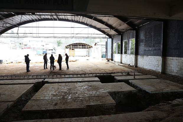 Center For The Arts remodel project personnel take a walk through tour of the center's progress last week showing the frame of the former car dealership above as well as the foundation work being done for the tech mezzanine below.