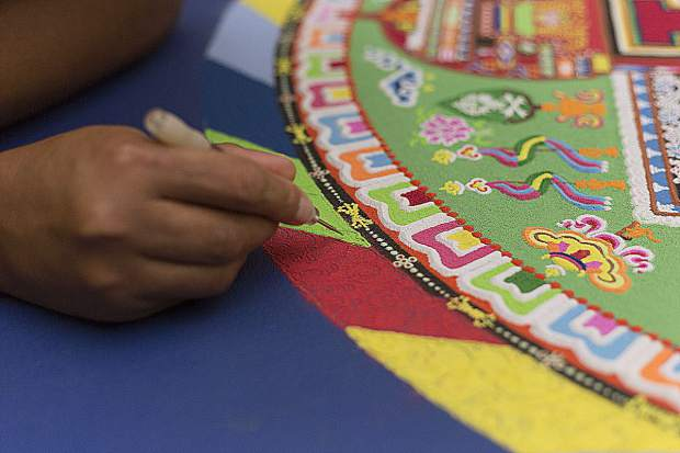 A Tibetan Monk drawing a sand mandala in Nevada County in years past.