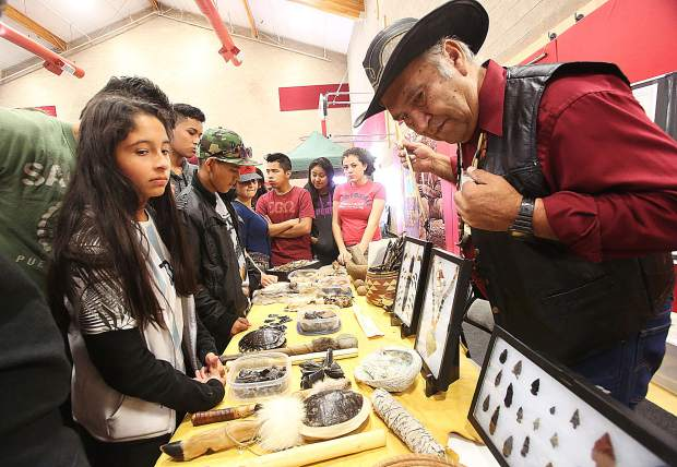 Local Nisenan Native American tribal elder Richard Johnson captives the imaginations of a table full of inquisitive youth interested in the displayed collection of Nisenan artifacts including obsidian arrowheads and knives, turtle shell rattles, and furs that were once used by the natives of Nevada County for thousands of years.