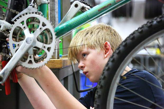 Roland Betito works on the crank assembly of a bicycle during a recent Seven Hills Middle School Bicycle Recycle Program class. The students use donated new and used materials to rebuild bicycles for charity projects.