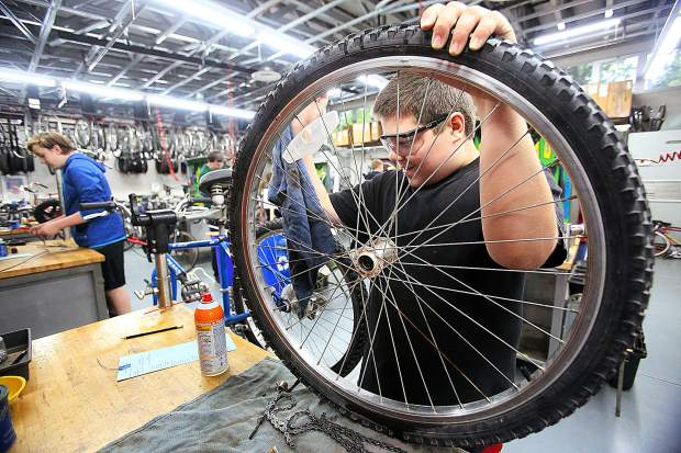Seven Hills Middle School's Adrian Zavaleta works on cleaning and greasing a wheel's bearing hub Wednesday in the school's bike shop.