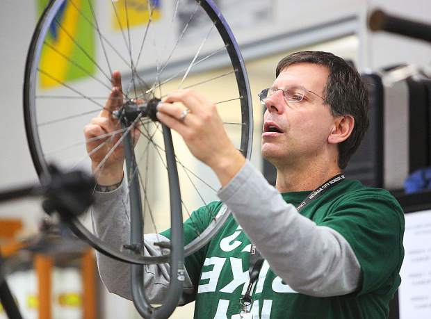 Bicycle Recycle instructor Steve Gillespie shows his class how a quick release works on a bicycle wheel.