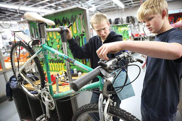Jackson Teitel and Roland Betito work together on a bike that is nearly ready to be donated for a local cause.