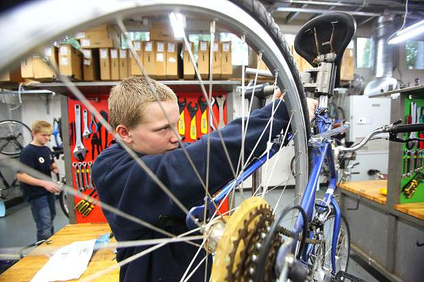 Seven Hills Middle School seventh-grader Jackson Teitel works on making adjustments to a bike during the school's Bicycle Recycle Program Wednesday. Under the tutelage of class instructor Steve Gillespie, students fix bikes to be donated to area homeless next year.