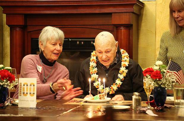 William Figara blows out the candles of his 100th birthday cake surrounded by his family Friday afternoon at Kane's Restaurant.