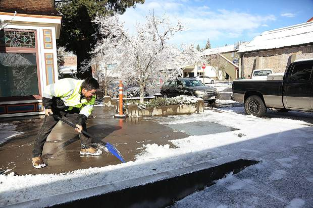 Luis Cobian of Cobian Landscaping shovels snow from in front of a business on Spring Street Thursday morning.