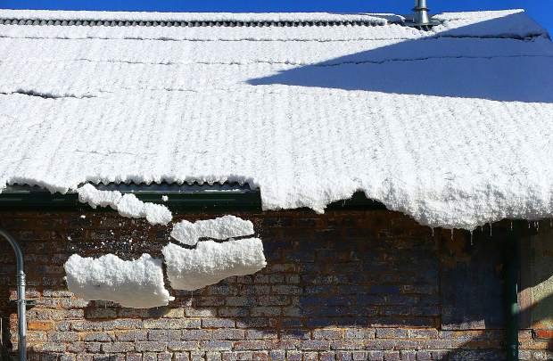 An eave of snow falls from the roof of a building in Nevada City Thursday morning.