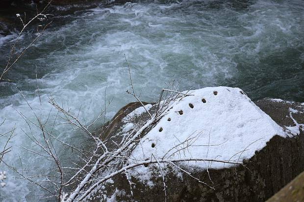 A boulder affected by mining efforts in Nevada City lies partially covered in snow in Deer Creek Thursday morning.