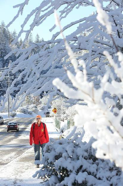 Grass Valley Atria Senior Living Center resident Don Belliss navigates the snow-covered sidewalks of Sutton Way as he makes his way toward the grocery stores of the Brunswick Basin Thursday morning. The lower elevations of Nevada County received a few inches of snow late Wednesday evening prompting area schools to close Thursday.
