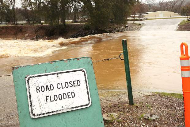 A road closed sign warns against any drivers attempting to cross Squirrel Creek through Western Gateway Park in Penn Valley during Tuesdays rain storms.