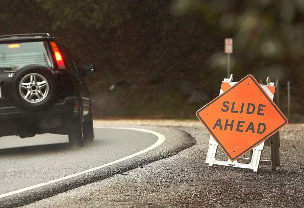 A vehicle makes its way down Highway 49 in the South Yuba River Canyon during Tuesday's rain. A rock and mud slide closed Highway 49 between Newtown Road in Nevada City to Tyler Foote Road on the San Juan Ridge for about an hour Tuesday morning.