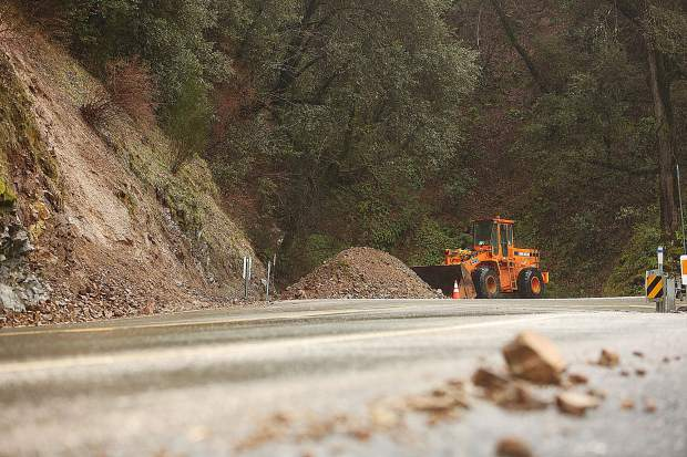 A mud and rockslide scar is visible alongside Highway 49 north of Newtown Road while a pile of the relocated mud awaits to be picked up and trucked away.