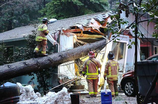 Nevada County and Nevada City firefighters work to assess a structure on the 11,000 block of Juniper Drive that sustained a large tree fall Tuesday evening, knocking out power and potentially causing a gas hazard in the process. Torrential rain and wind caused multiple downed trees and power outages in Nevada County Tuesday.