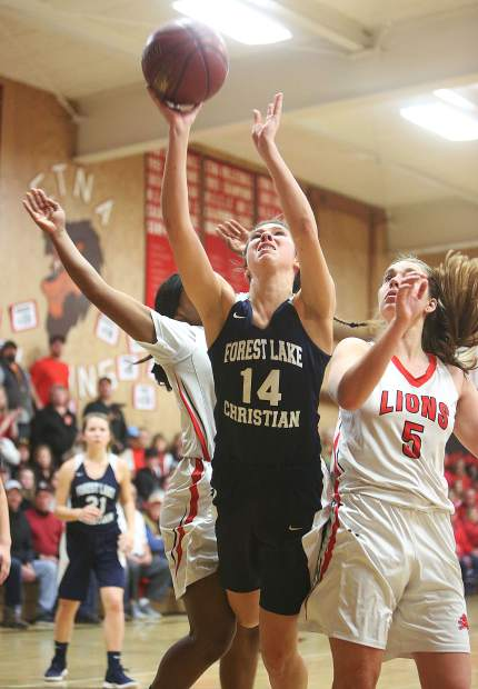 Forest Lake Christian's Lily Sween is fouled on her way to the basket by a pair of Etna Lions defenders.