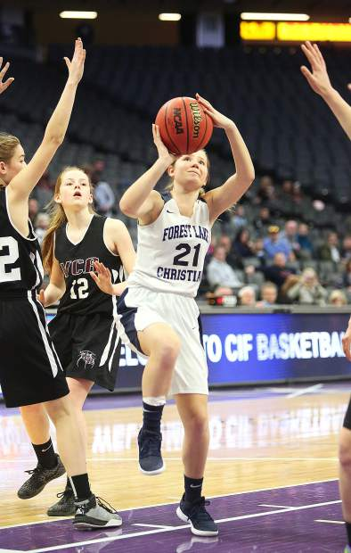Forest Lake Christian shooting guard Ellie Wood (21) takes a shot on the hoop from the floor of the Golden 1 Center arena in Sacramento during Friday's D VI championship game.