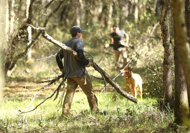 Volunteers gathered brush and branches cut away from the path of the new bike park being built around the dog park at Western Gateway Park in Penn Valley.