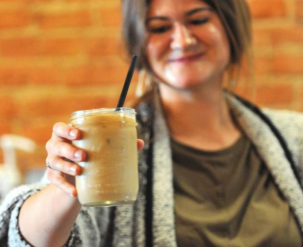 Brew Bakers employee Natalee Heilaman presents an iced latte to a customer Thursday afternoon.