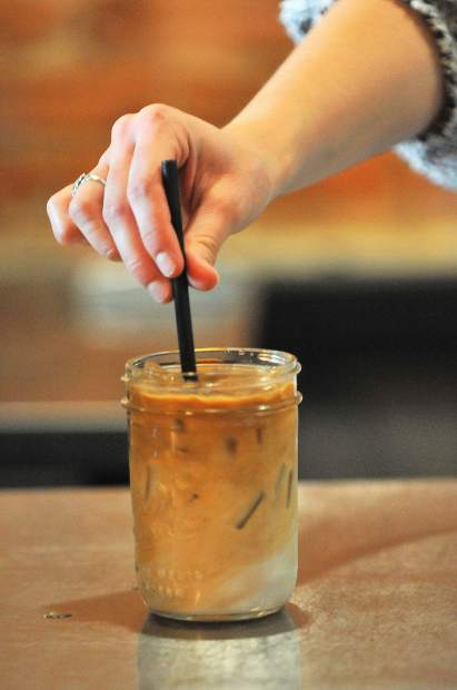 Brew Bakers employee Natalee Heilaman puts the finishing touches on an iced latte Thursday afternoon.