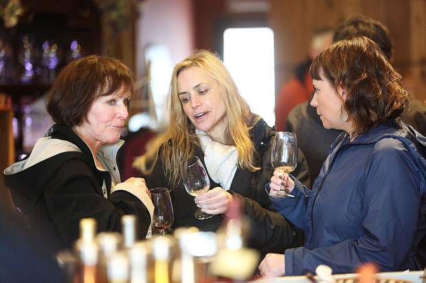 Collette Swaringen (from left), Melisa Meyer, and Jamie Reeves chat and sip wine in downtown Grass Valley during Saturday's Foothills Celebration.