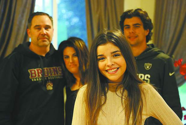 Emily Bucher smiles as she stands in front of her father Jake, mother Traci, and brother Chad.