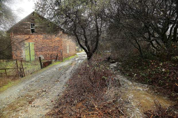 A tributary of French Corral Creek jumps its banks and flows down the old ruts of a road behind the 1853 Wells Fargo and Co. building in French Corral.