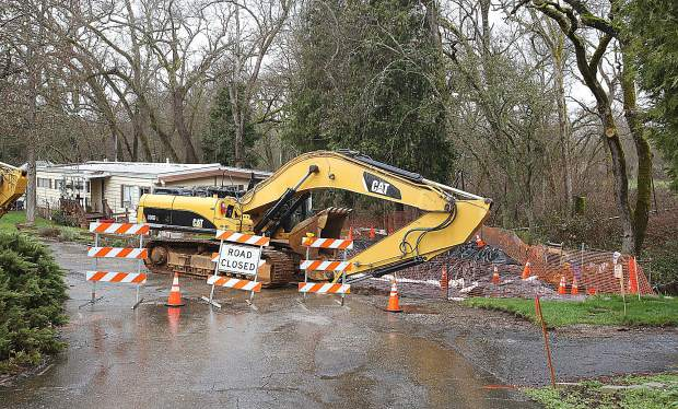 A road is blocked in Penn Valley's Creekside Mobile Home Village where a sinkhole has opened up next to a home where Squirrel Creek flows nearby.