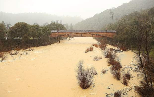 A milk chocolate colored South Yuba River — laden with sediment — flows high and fast under the historic Bridgeport Covered Bridge in the South Yuba River State Park Wednesday afternoon. The waters of the Yuba, along with every other north Sierra Nevada waterway, are rushing towards the Sacramento Valley prompting flood watches and advisories.