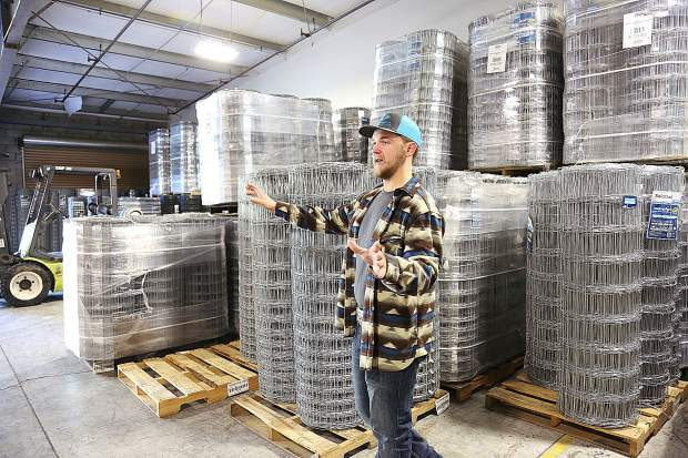 Conner Olson stands in front of a large inventory of different heights of galvanized fencing located in Live Wire's Penn Valley warehouse.