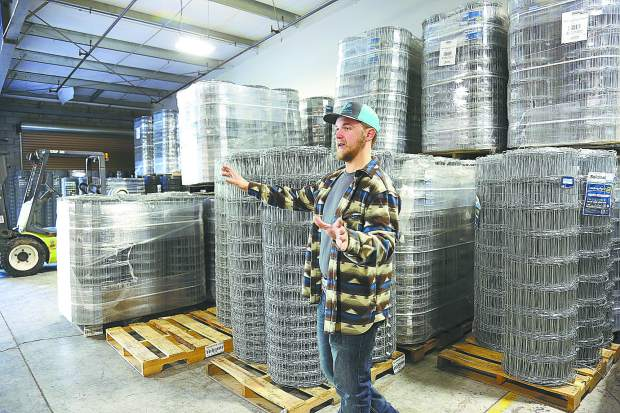 Conner Olson stands in front of a large inventory of different heights of galvanized fencing located in their Penn Valley warehouse.